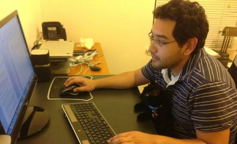 Image of man searching on internet with cat