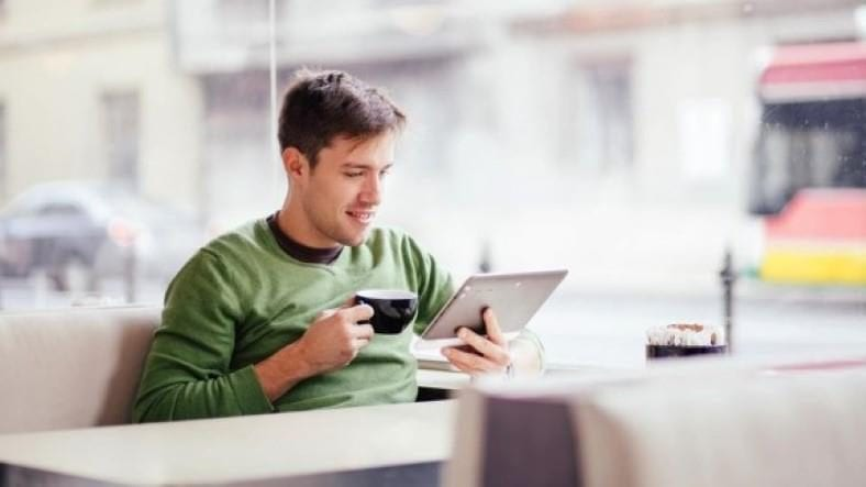 Image of man casually shopping online with a tablet